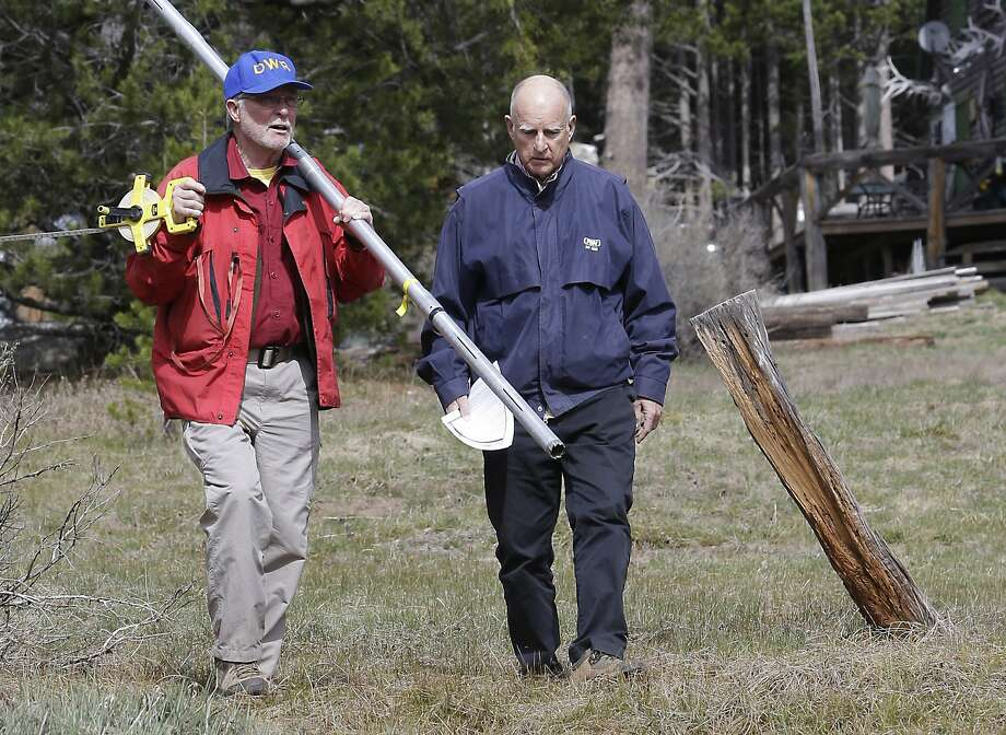 Frank Gehrke, left, chief of the California Cooperative Snow Surveys Program for the Department of Water Resources, and Gov. Jerry Brown walk across a dry meadow that is usually covered in several inches of snow as conducts the snow survey, near Echo Summit, Calif., Wednesday, April 1, 2015. Gehrke said this was the first time since he has been conducting the survey that he found no snow at this location at this time of the year.  Brown took the occasion to annouced that he signed an executive order requiring the state water board to implement measures in cities and towns to cut water usage by 25 percent compared with 2013 levels. (AP Photo/Rich Pedroncelli) Photo: Rich Pedroncelli, Associated Press