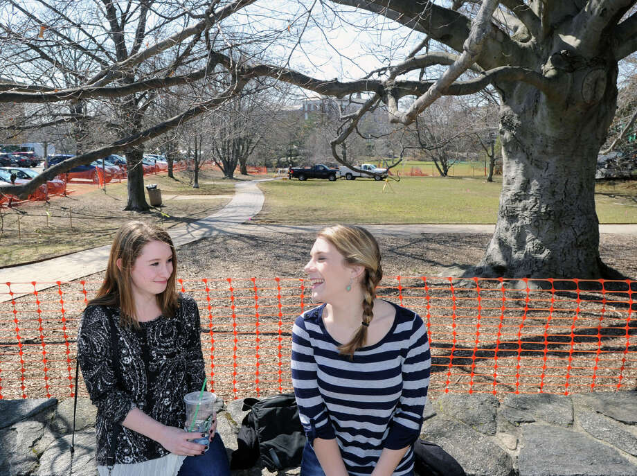At left, Meghan MacKay, 16, and Sophie Cozine, 19, both of Wilton, sit on the stone wall that is a boundary of the Greenwich Common, Conn., Thursday, April 2, 2015. Starting on Monday, April 6, Greenwich Common will be closed for three to four months of constructive improvement as announced by the Greenwich Dept. of Public Works Engineering Division and the Dept. of Parks & Recreation. Photo: Bob Luckey / Greenwich Time