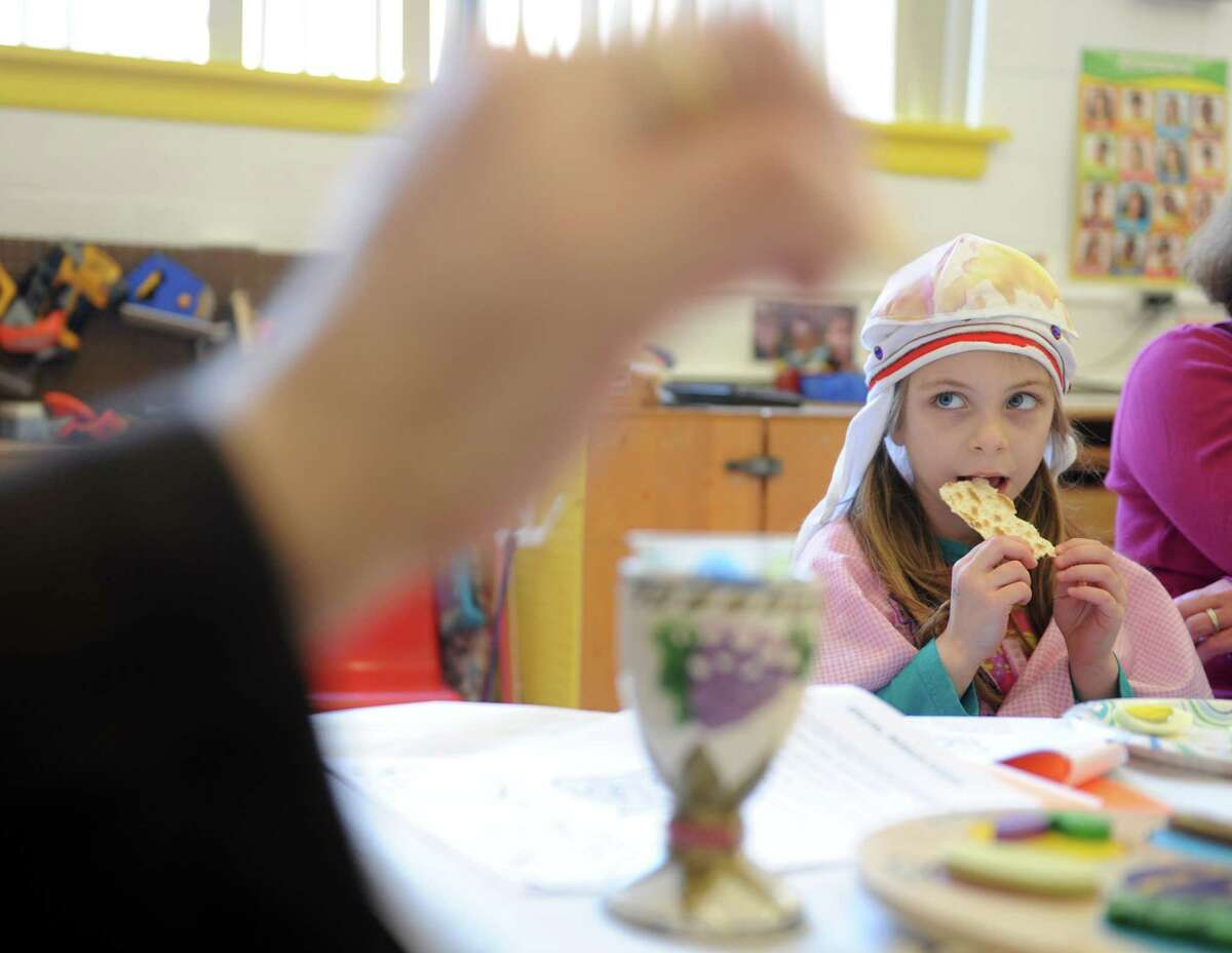Four-year-old Sally Pelligra eats matzoh as she learns about Passover from Rabbi Colin Brodie Thursday, April 2, 2015, during a model seder at Congregation B'Nai Torah in Trumbull, Conn.