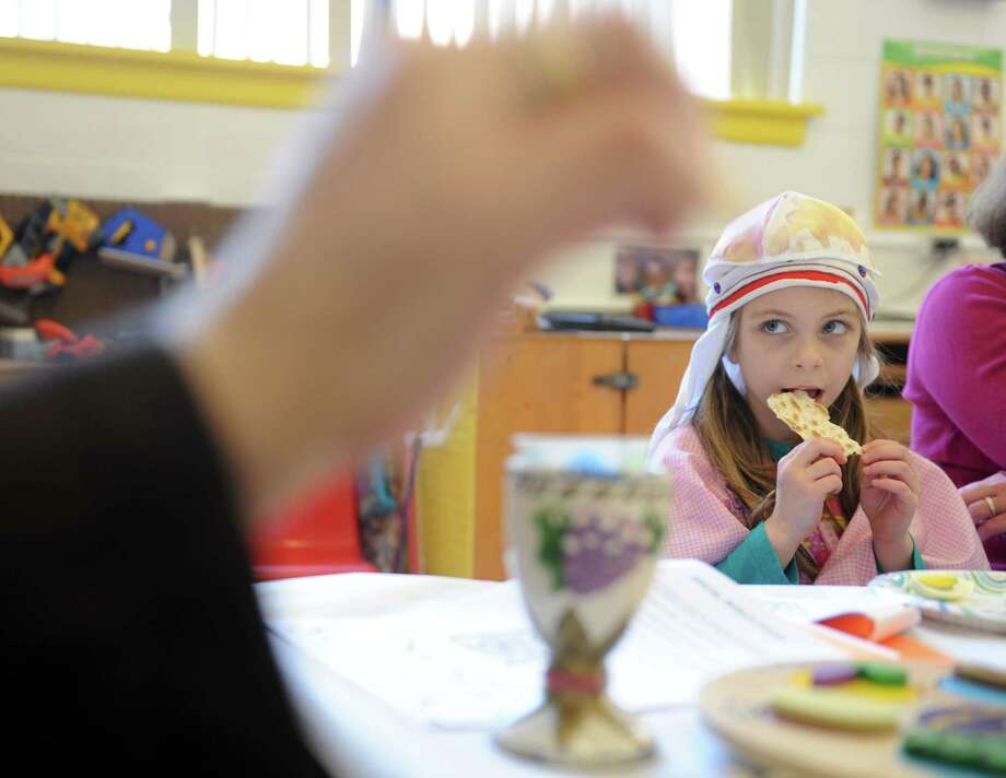 Four-year-old Sally Pelligra eats matzoh as she learns about Passover from Rabbi Colin Brodie Thursday, April 2, 2015, during a model seder at Congregation B'Nai Torah in Trumbull, Conn. Photo: Autumn Driscoll / Connecticut Post