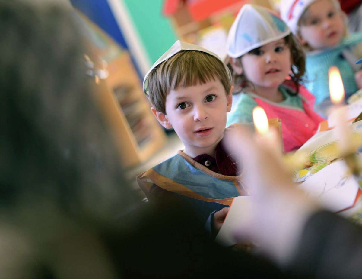 Four-year-old Ryan Levine and his nursery school classmates learn about Passover from Rabbi Colin Brodie Thursday, April 2, 2015, during a model seder at Congregation B'Nai Torah in Trumbull, Conn.