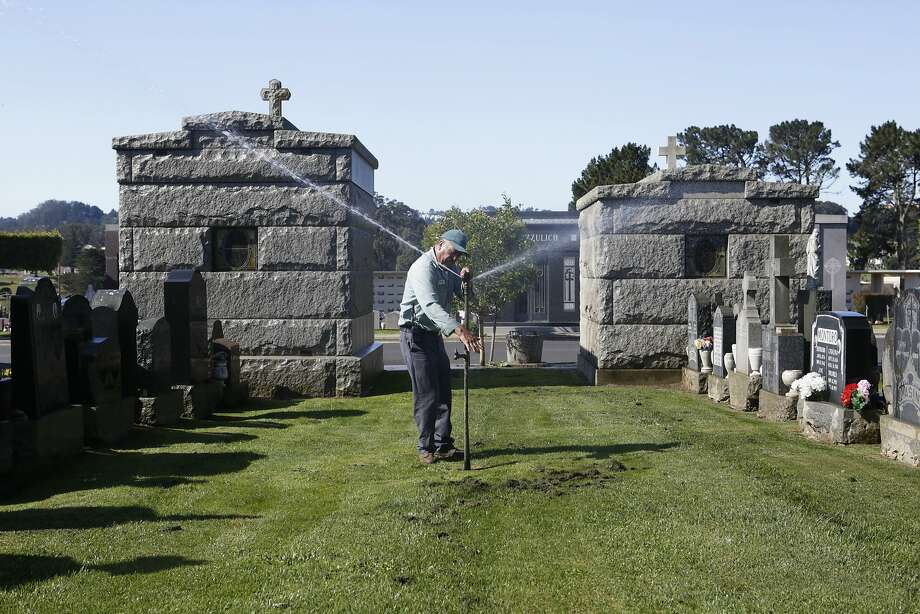 Groundskeeper Filiberto Garcia adjusts a sprinkler in the Italian Cemetery in Colma, CA, on Thursday, April 2, 2015. Many cemeteries will have to adapt after California Governor Jerry Brown announced on Wednesday that water agencies in the state will be required to cut usage by 25 percent. Photo: Terray Sylvester, The Chronicle