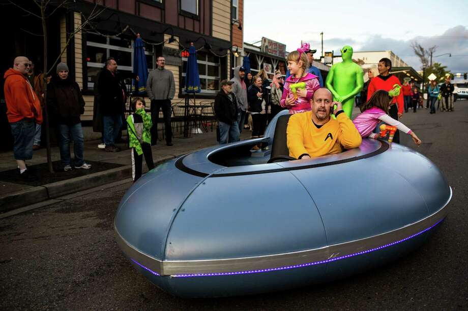 "Casually skirting ""street closed"" signs, a man and his daughters park their road-operational flying saucer at the annual Burien UFO Festival on April Fool's Day, Wednesday, April 1, 2015, in Olde Burien, Washington. The quirky evening event included a 3-D flying saucer, flash mob dance and a cash costume contest for aliens and ""G Men"" alike. Photo: JORDAN STEAD, SEATTLEPI.COM / SEATTLEPI.COM"
