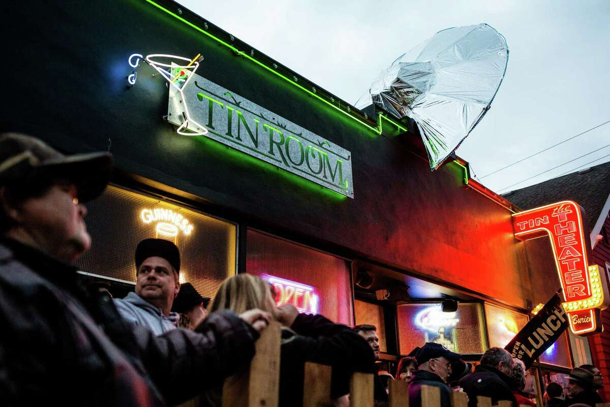Eventgoers enjoy beers below a fabricated crashed flying saucer at the annual Burien UFO Festival on April Fool's Day, Wednesday, April 1, 2015, in Olde Burien, Washington. The quirky evening event included a 3-D flying saucer, flash mob dance and a cash costume contest for aliens and