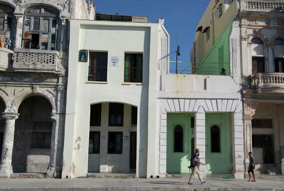 Tourists walk beside two privately owned houses with rooms for rent in Havana, Cuba, Wednesday, April 1, 2015. The wildly popular online home-sharing service Airbnb will allow American travelers to book lodging in Cuba starting Thursday in the most significant U.S. business expansion on the island since the declaration of detente between the two countries late last year. (AP Photo/Desmond Boylan) Photo: Desmond Boylan / Associated Press / AP