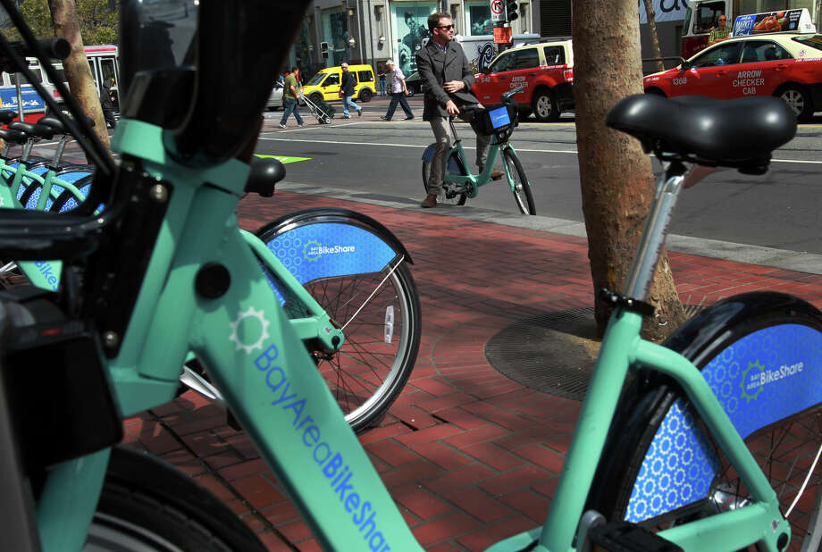 Brendan Monghan prepares to ride a Bike Share bicycle to work in S.F., which could get 4,000 more bikes. Photo: Leah Millis / The Chronicle / ONLINE_YES