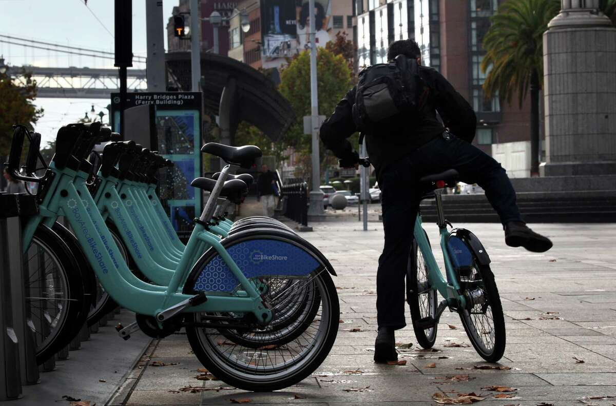 A commuter uses the Bay Area Bike Share station at Harry Bridges Plaza in San Francisco to get to work on Nov. 12, 2013.
