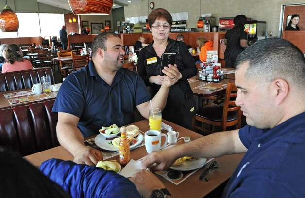Denny's customer Chris Gonzales of Latham shows a cellphone photo to waitress Kathy Morgan while having lunch with his brother Peter Gonzalez and Peter's wife Parishisma also of Latham on Wednesday, March 11, 2015 in Colonie, N.Y. Kathy has been a waitress at this Denny's for 40 years. (Lori Van Buren / Times Union) Photo: Lori Van Buren / 10030877A