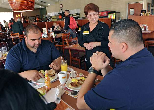Denny's waitress Kathy Morgan talks to regular customers Chris Gonzales, left, his brother Peter Gonzalez and Peter's wife Parishisma all from Latham on Wednesday, March 11, 2015 in Colonie, N.Y. Kathy has been a waitress at this Denny's for 40 years. (Lori Van Buren / Times Union) Photo: Lori Van Buren / 10030877A