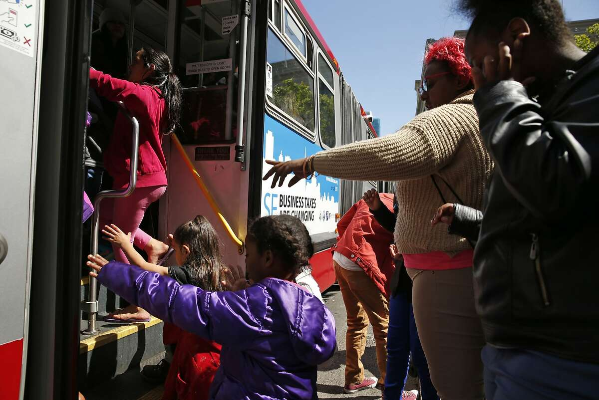 Commuters board a MUNI bus on Cyril Magnin Street in San Francisco, Calif., on Thursday, April 2, 2015.