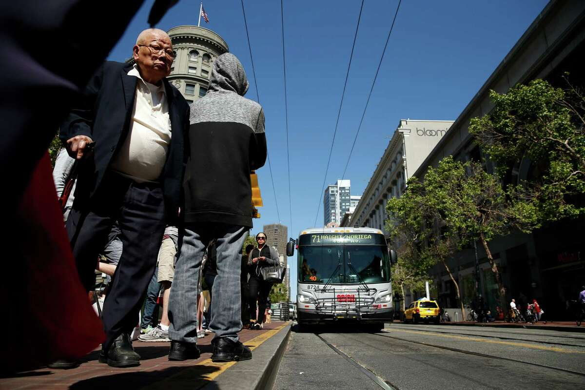 Commuters wait at a Muni bus stop on Market Street in San Francisco Thursday.