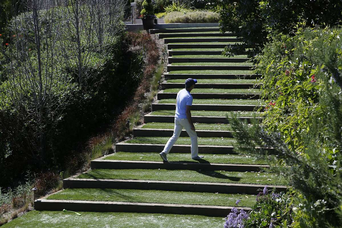 Gary Graw, owner of Green Space Grass, walks part of an expansive synthetic lawn he installed at Steven and Katherine Van Dusen's home in Tiburon, CA, on Thursday, April 2, 2015. The Van Dusens had an acre of the plastic turf installed in 2010 to defray watering costs. Many California homeowners may have to adapt after Governor Jerry Brown announced on Wednesday that water agencies in the state will be required to cut usage by 25 percent.