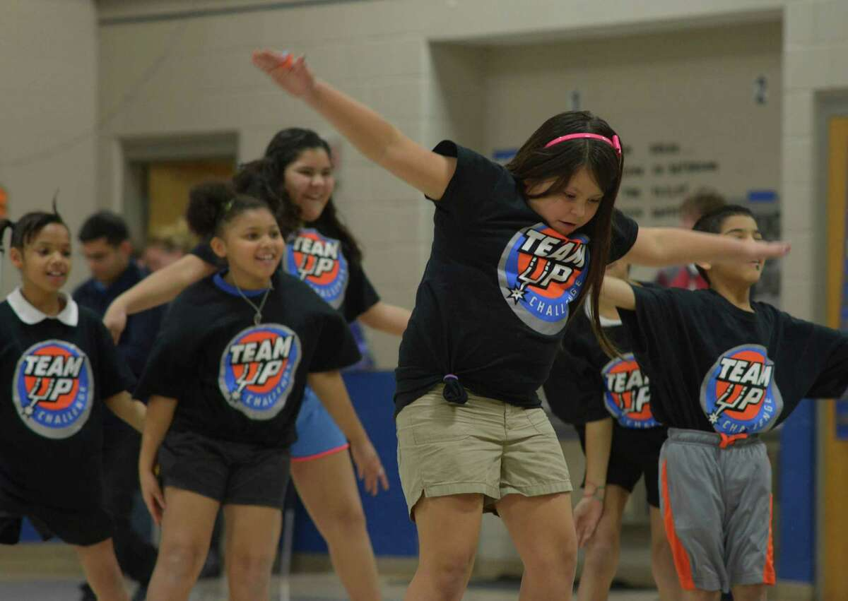Daily exercise is key to battling obesity in the Hispanic community. Smith Elementary School students participating in the Silver & Black Give Back Team Up Challenge exercise in the gym on Jan. 7.
