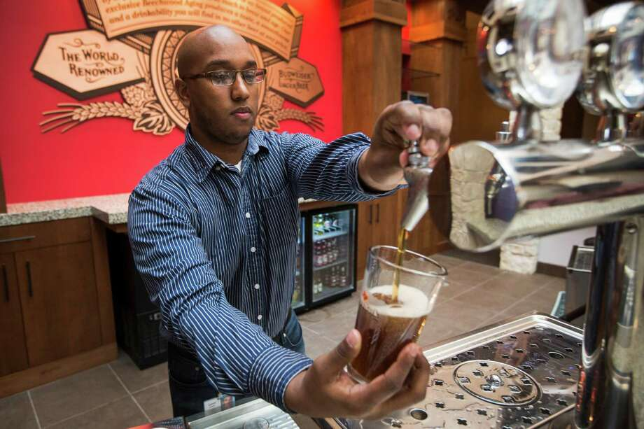 Aaron West, tour manager, pours a beer in the remodeled and reopened tasting room at the Anheuser-Busch Brewery on Thursday. The brewery will soon resume tours. Photo: Brett Coomer, Staff / © 2015 Houston Chronicle