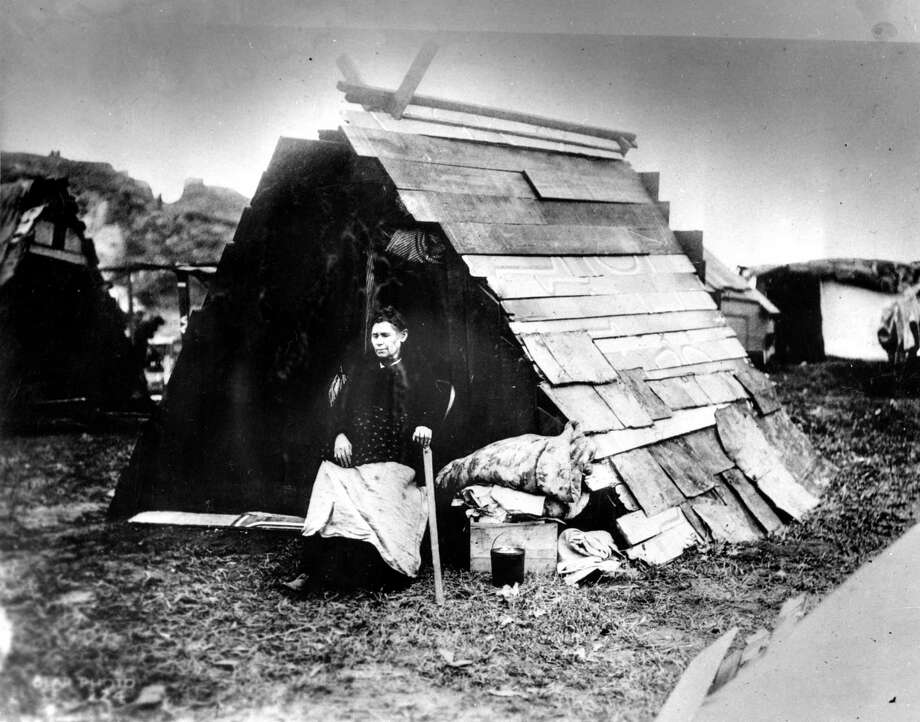1906 earthquake photo from The San Francisco Chronicle archive. Photographer unknown. Woman in front of her A-frame shack in a refugee camp. Photo: Chronicle Archives / ONLINE_YES