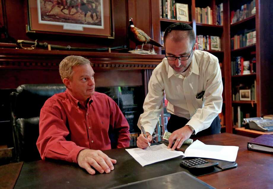 "Dave Clark, of West University Baptist Church, and neighbor Rabbi Ranon Teller, of Brith Shalom, sign an official document for selling ""chametz.""  Photo: Gary Coronado, Staff / © 2015 Houston Chronicle"