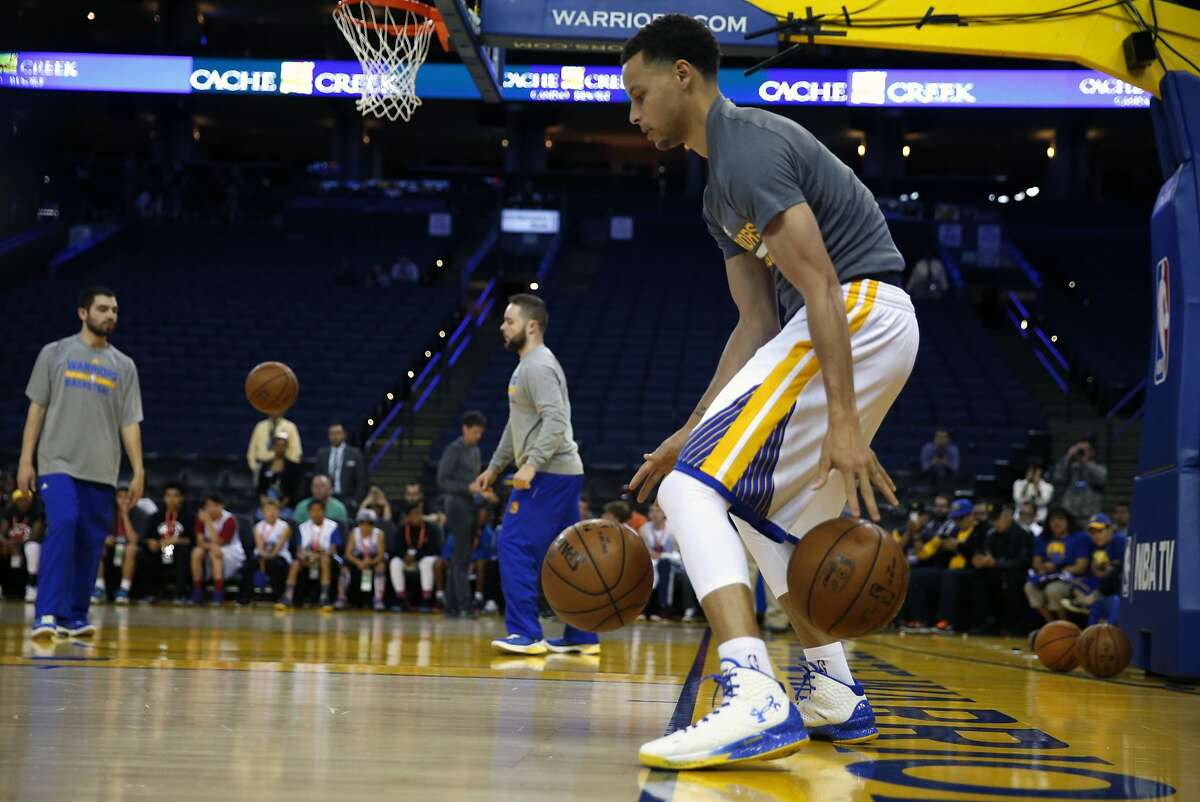 Golden State Warriors' Stephen Curry dribbles two balls as part of his pre-game ritual before playing Phoenix Suns during NBA game in Oakland, Calif., on Thursday, April 2, 2015.