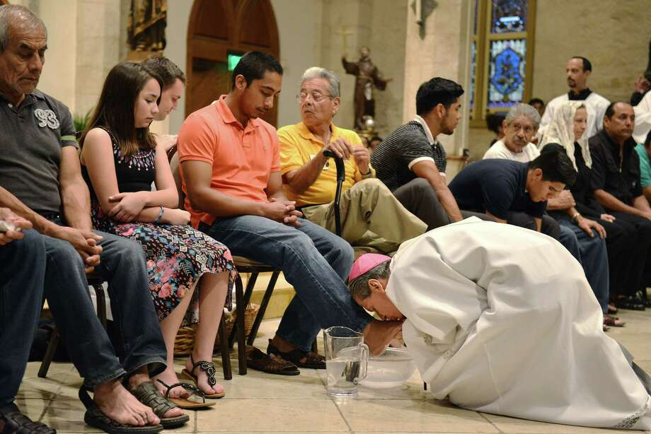 Archbishop Gustavo Garcia-Siller kisses and washes the feet of Emmanuel Quijano and other members of the congregation at San Fernando Cathedral on Holy Thursday, April 2, 2015 in San Antonio. Emmanuel Quijano, will be playing Jesus in the passion play tomorrow. Photo: Matthew Busch, For The San Antonio Express-News / © Matthew Busch