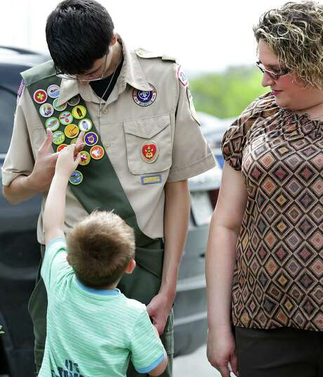 Dakota Freeman-Wright, 4, asks his brother Nick Zamora about his badges as their mother, Adella Freeman, looks on.  Freeman, who is gay, was kicked out of the Boy Scouts meetings as her son was gearing up to become an Eagle Scout.  Photo: Bob Owen, Staff / © 2015 San Antonio Express-News