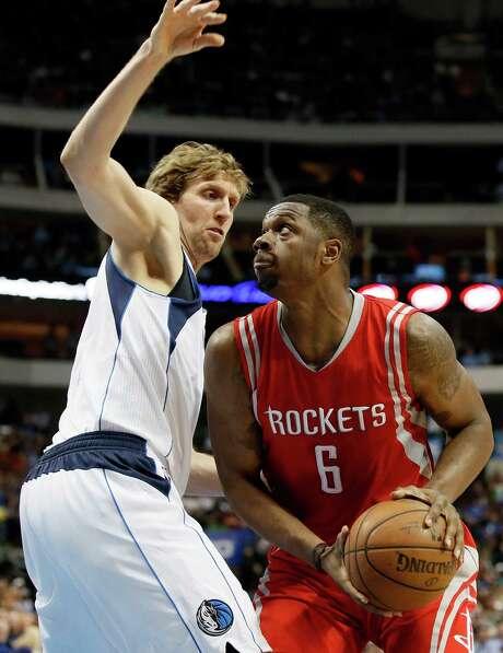 Rockets forward Terrence Jones prepares to take it to the glass over the Mavericks' Dirk Nowitzki. Jones had seven points as the Rockets won at Dallas. Photo: Tony Gutierrez, STF / AP