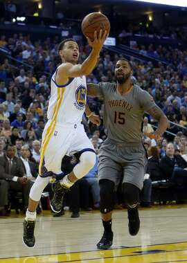 Golden State Warriors' Stephen Curry scoops a shot against Phoenix Suns' Marcus Morris in 1st quarter during NBA game at Oracle Arena in Oakland, Calif., on Thursday, April 2, 2015.