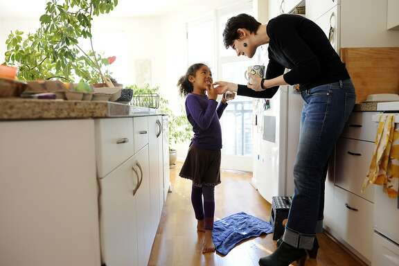 Martha Rynberg takes a look at a loose tooth of her daughter Carter., 6, in the kitchen of their apartment in the Uptown area of Oakland, CA, on Monday, April 2, 2015.