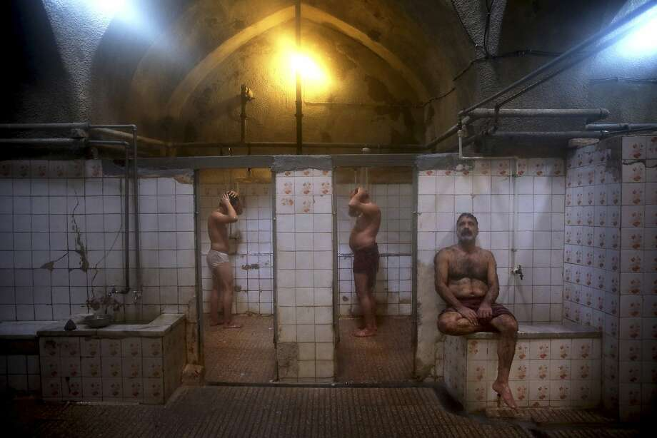 """In this Jan. 9, 2015 photo, patrons shower at the Ghebleh public bathhouse, in Tehran, Iran. The hammams find themselves in rough financial times as modern conveniences now allow showers and baths in most homes across the Islamic Republic. In the old days, the bathhouses functioned more than just a place to clean up, shave or get a massage from a """"dallak,"""" a masseuse who uses a mitt to scrub and exfoliate a client's body, people gathered in the humid air to discuss current events and debate ideas. (AP Photo/Ebrahim Noroozi) Photo: Ebrahim Noroozi, Associated Press"""