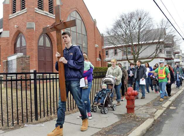 Adam Konicki, 16, left, leads the Mont Pleasant Good Friday Cross Walk past the Faith Deliverance Tabernacle Church on Crane Street Friday April 3, 2015 in Schenectady, NY.  (John Carl D'Annibale / Times Union) Photo: John Carl D'Annibale / 00031266A
