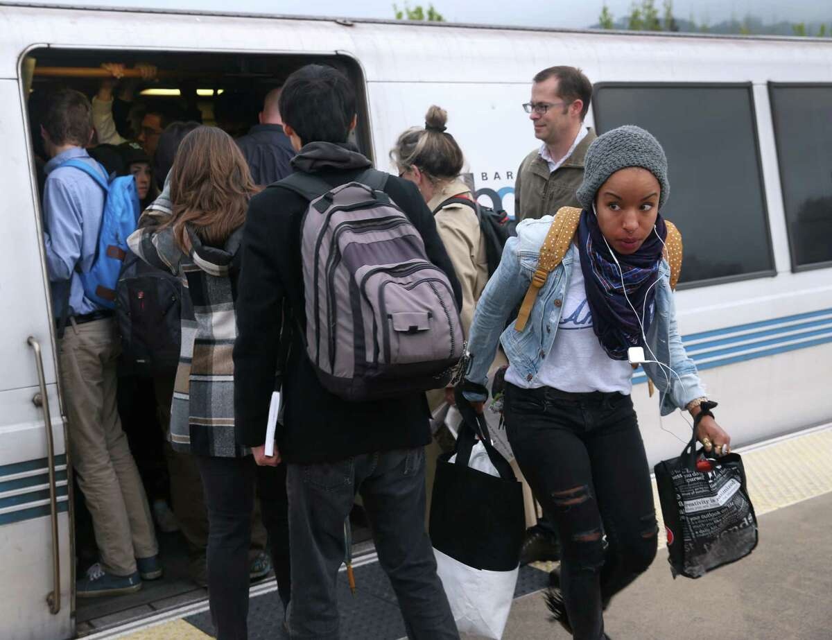 A passenger (right) getting off at the Rockridge BART station has to navigate through a crush of commuters trying to board a San Francisco train in Oakland, Calif. on Tuesday, March 24, 2015. Ridership continues to rise on the regional transit system.