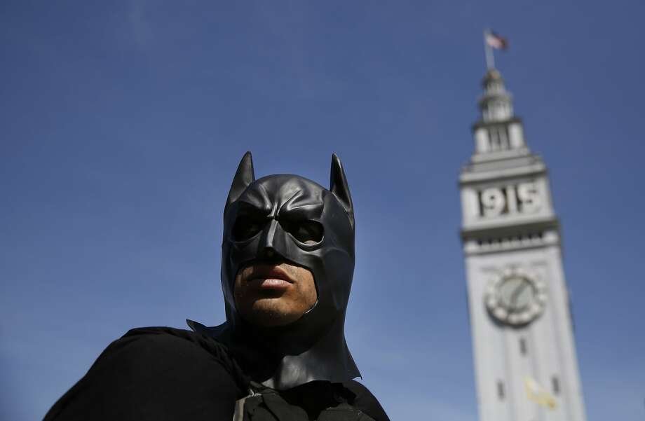 Dressed as Batman, Jorge Olascoaga wheels his pedicab near the Ferry building looking for businesses in San Francisco, Calif. Photo: Mike Kepka, The Chronicle