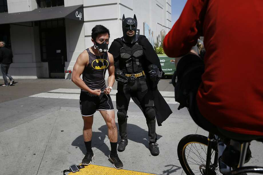 Jacky Chan, of San Francisco, stops his workout to get a pictures with Golden Gate Pedicab driver Jorge Olascoaga dressed as Batman on the Embarcadero in San Francisco, Calif. Photo: Mike Kepka, The Chronicle