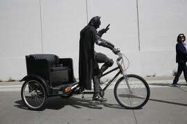 Dressed as Batman, Jorge Olascoaga tries to drum up business on his pedicab on the Embarcadero in San Francisco, Calif.