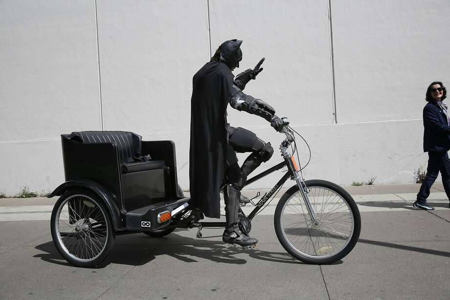 Dressed as Batman, Jorge Olascoaga tries to drum up business on his pedicab on the Embarcadero in San Francisco, Calif. Photo: Mike Kepka, The Chronicle