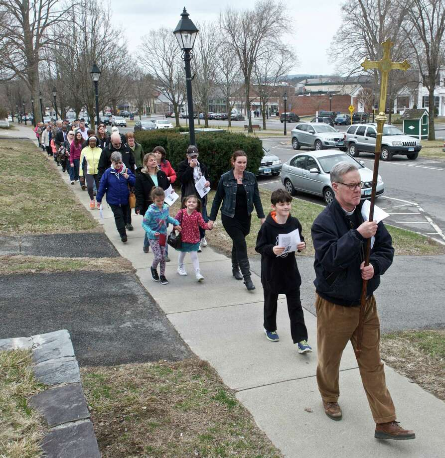 Carrying the cross the Rev. Jack Gilpin leads the annual New Milford Good Friday Christian Faith Walk  up Whittlesey Ave. along the green in New Milford, Conn, on Friday, April 3, 2015. Rev. Gilpin is the priest in charge of St. John's Episcopal Church, in New Milford. Photo: H John Voorhees III / The News-Times