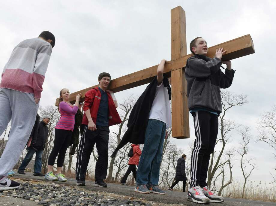 Daniel Lepoutre, right, 16, and others carry a cross into Greenwich Point Park for the Good Friday Youth Cross Walk in Old Greenwich, Conn. Friday, April 3, 2015.  As a Good Friday tradition, church kids carried a large wooden cross from First Congregational Church of Greenwich to the beach at Greenwich Point Park.  The cross will be used for the church's Easter Sunday sunrise service at Greenwich Point Park at 6:15 a.m. Photo: Tyler Sizemore / Greenwich Time
