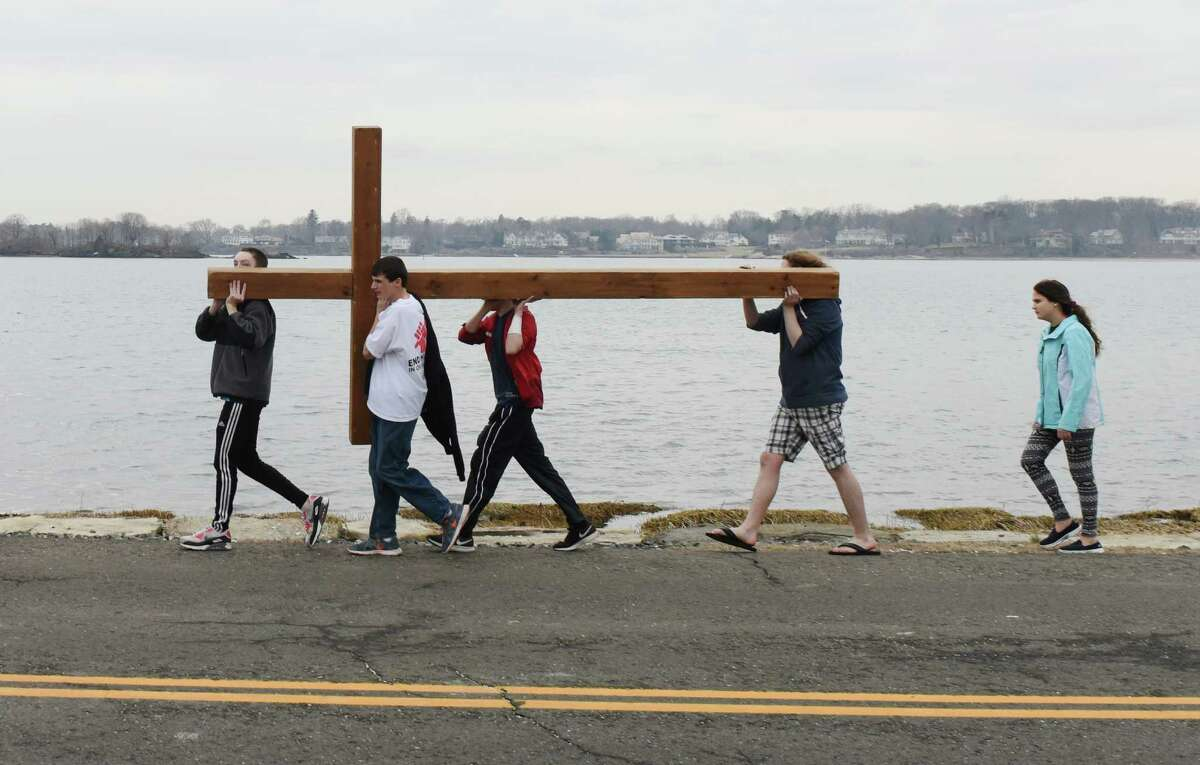 Youths carry a cross into Greenwich Point Park for the Good Friday Youth Cross Walk in Old Greenwich, Conn. Friday, April 3, 2015. As a Good Friday tradition, church kids carried a large wooden cross from First Congregational Church of Greenwich to the beach at Greenwich Point Park. The cross will be used for the church's Easter Sunday sunrise service at Greenwich Point Park at 6:15 a.m.