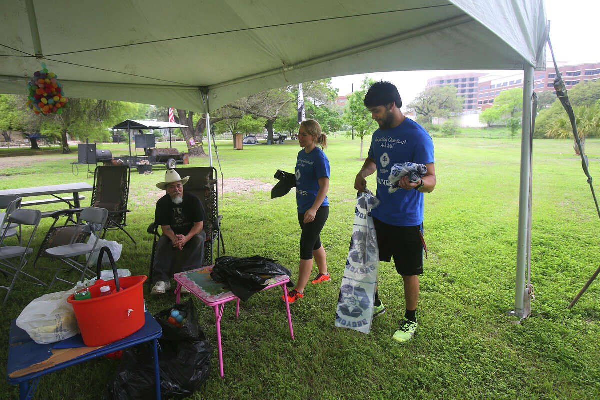 Volunteers Nikki Merrill (center) and A.J. Martinez (right) deliver free trash and recycle bags Friday April 3, 2015 to the camp site of Danny Garza (seated) at Brackenridge Park before Easter weekend. Merrill and Martinez are U.T.S.A. students and volnteered to work for the city to help keep the park clean.