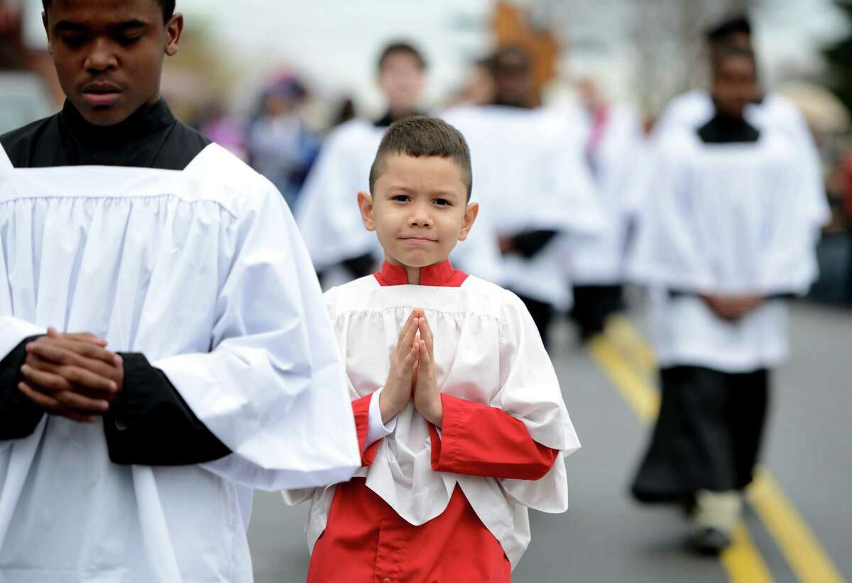 Eight-year-old Andrew Ramirez, of Bridgeport, walks down Pequonnock Street in Bridgeport Friday, April 3, 2015, as he participates in the annual Good Friday procession which began at St. Augustine Cathedral on Washington St. and ended at St. Patrick Church on North Ave.