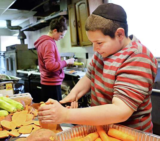 Eleven-year-old Aharon Meir Morrison, right, and his sister Orley, 15, peel vegetables for a Seder soup in the kitchen of the historic Beth Tephilah Friday April 3, 2015 in Troy, NY.  (John Carl D'Annibale / Times Union) Photo: John Carl D'Annibale / 00031299A