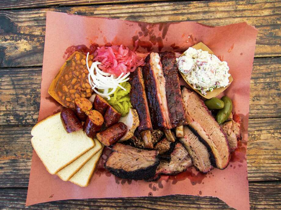A spread of barbecue made by John Lewis at La Barbecue in Austin, above. Franklin Barbecue in Austin, left, is open Wednesdays-Sundays from 11 a.m. to 4 p.m. or until it runs out of food. Photo: J.C. Reid