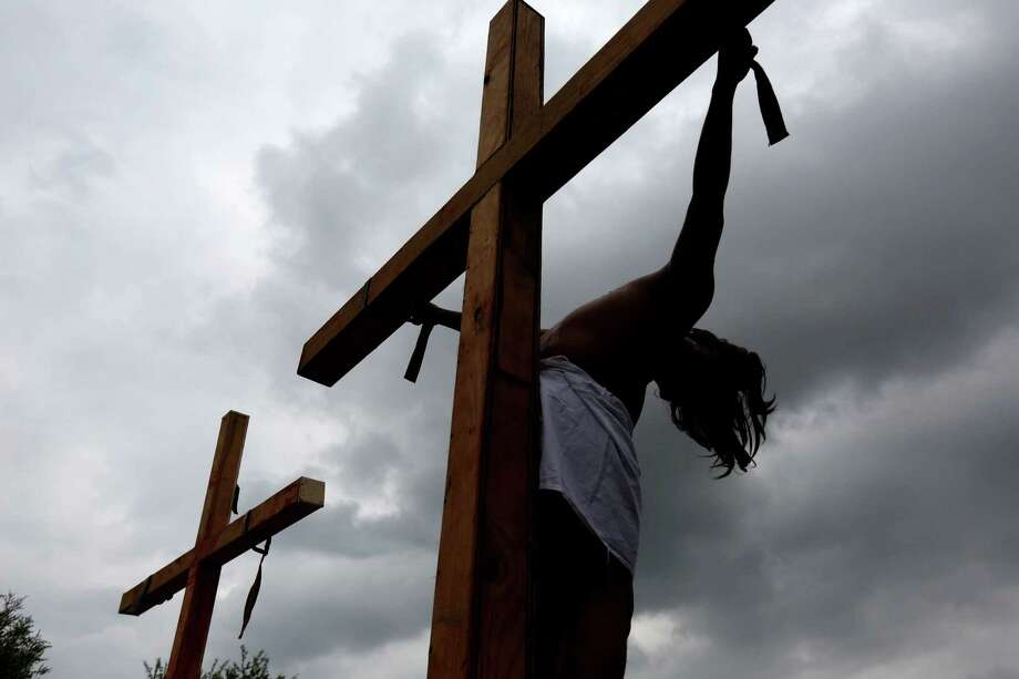 The cross of Jorge Martinez, as Christ, is vacant after being removed while parishioners portray the Passion of Christ, the short final period in the life of Jesus covering his visit to Jerusalem and leading to his execution by crucifixion, at Queen of Peace Catholic Church on Good Friday, April 3, 2015, in Houston, Texas. Photo: Gary Coronado, Houston Chronicle / © 2015 Houston Chronicle