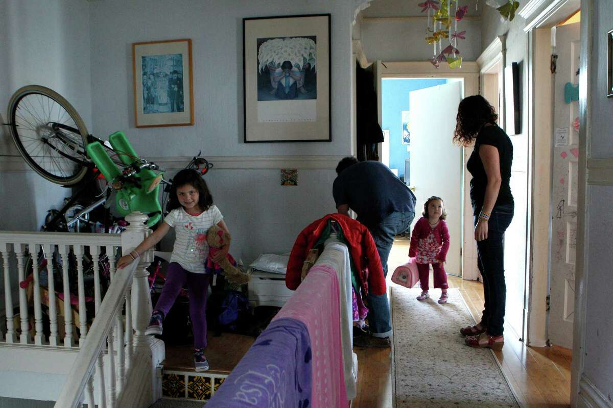 Marina Lopez-Salazar (left), age 6, and Camila Lopez-Salazar, age 3, head out with their parents Leila Salazar (right) and Ariel Lopez, at their apartment in the Mission neighborhood, Friday, April 3, 2015, in San Francisco, Calif. The family narrowly avoided eviction and fear that they could be in the future. S.F. supervisor David Campos has floated the idea of imposing a temporary moratorium on new development in a roughly 10 square block area in the Mission district. The idea is to halt new development until the city can develop a comprehensive plan about how to deal with the housing crisis that has removed longtime residents from their homes.