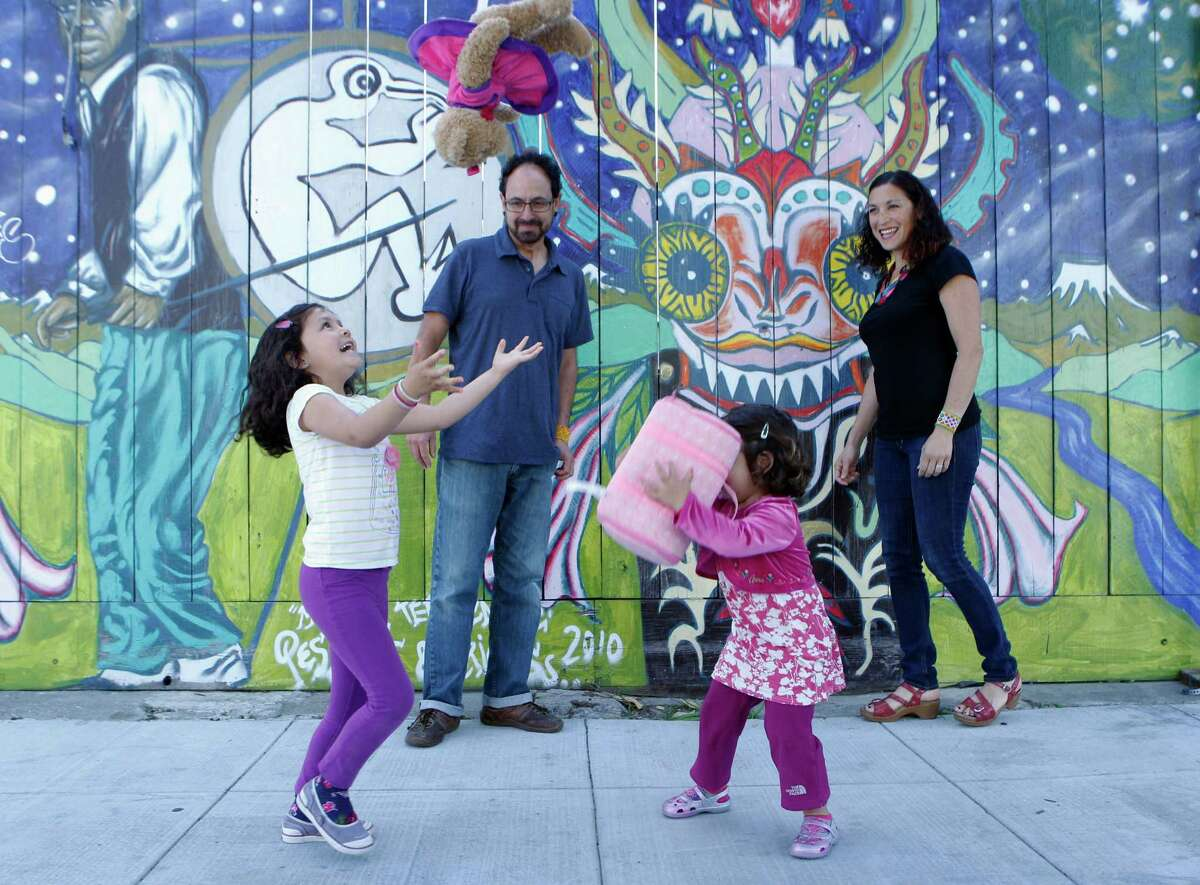 Marina Lopez-Salazar (left), age 6, and Camila Lopez-Salazar, age 3, play with their parents Leila Salazar (right) and Ariel Lopez, near their apartment in the Mission neighborhood, Friday, April 3, 2015, in San Francisco, Calif. The family narrowly avoided eviction and fear that they could be in the future. S.F. supervisor David Campos has floated the idea of imposing a temporary moratorium on new development in a roughly 10 square block area in the Mission district. The idea is to halt new development until the city can develop a comprehensive plan about how to deal with the housing crisis that has removed longtime residents from their homes.