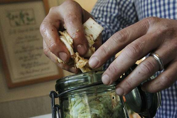 After Russell Moore tosses and mixes all of the ingredients in a bowl, then he squishes the mixture into a jar and lets it ferment for a few days in his home in Richmond, Calif., Thursday April 2, 2015.