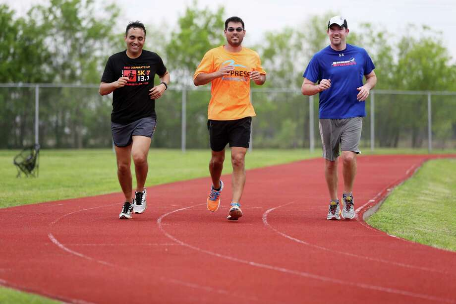 J.P. Giometti, from left, Jose Barbosa and Skyler Moss run on the HCSS track during lunch. The company offers its employees monetary incentives as well as a variety of fitness classes to promote healthy lifestyles. Photo: Mayra Beltran, Staff / © 2015 Houston Chronicle