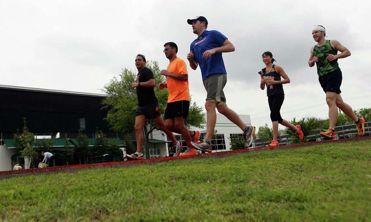 Co-workers J.P. Giometti, Jose Barbosa, Skyler Moss, Amy Chien and Zack Foster run laps after a fitness class during lunch at HCSS, a company that promotes wellness by providing running path around the perimeter of the office, fitness classes with personal trainers, boot camps, strength training, zumba, and even meditation classes on Wednesday, April 1, 2015, in Houston. ( Mayra Beltran / Houston Chronicle )