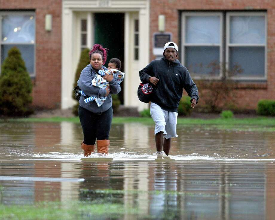 Kevin Mansfield, right, helps guide Simone Wester and her 7-month old son Jeremiah from her flooded apartment building at the Guardian Court Apartments in Louisville, Ky., on Friday. Photo: Timothy D. Easley, FRE / FR43398 AP