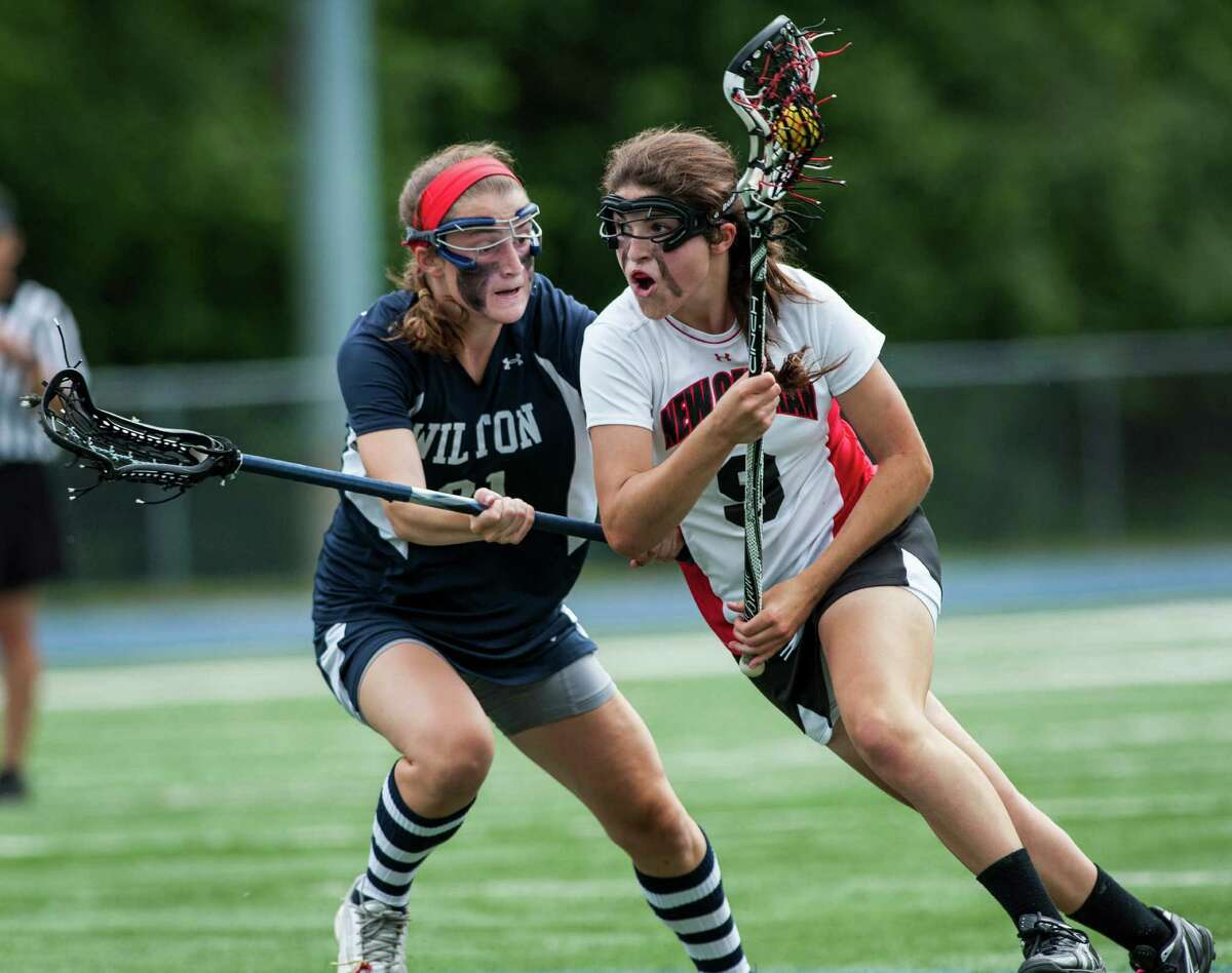 New Canaan high school's Isabel Taben tries to get by Wilton high school's Maeve Kennard during the CIAC division M girls lacrosse championship game played at Bunnell high school, Stratford, CT on Saturday June 8th, 2013.