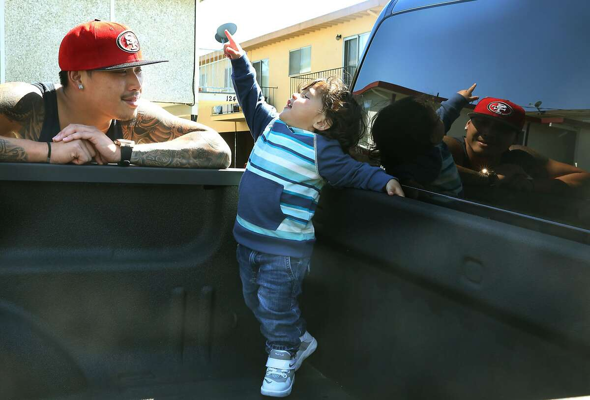 Kevin Yip playing with his 22 month old son, Dominic King Yip in front of his parents' home where he grew up in San Bruno, California, on Friday, April 3, 2015.