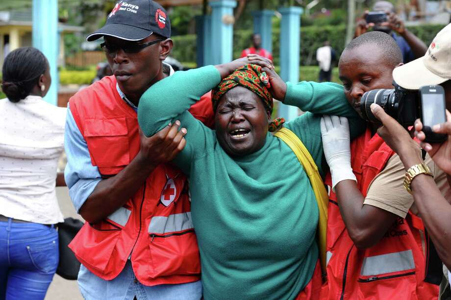 Kenya Red Cross staffers assist a woman after she viewed the body of a relative killed at Garissa University College. The country's interior minister said 142 of the 148 people killed were students. Photo: Associated Press / AP